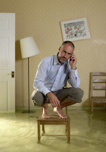 man on chair because basement carpet is flooded